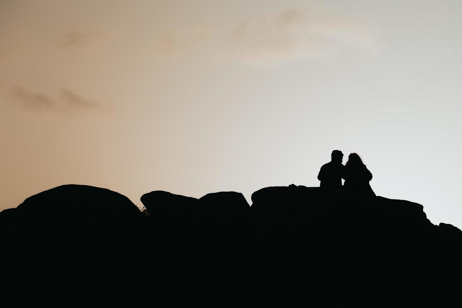 silhuett av ett par över en färgglad solnedgång foto