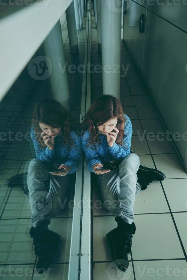 ung kvinna ensam och trött på en busstation foto