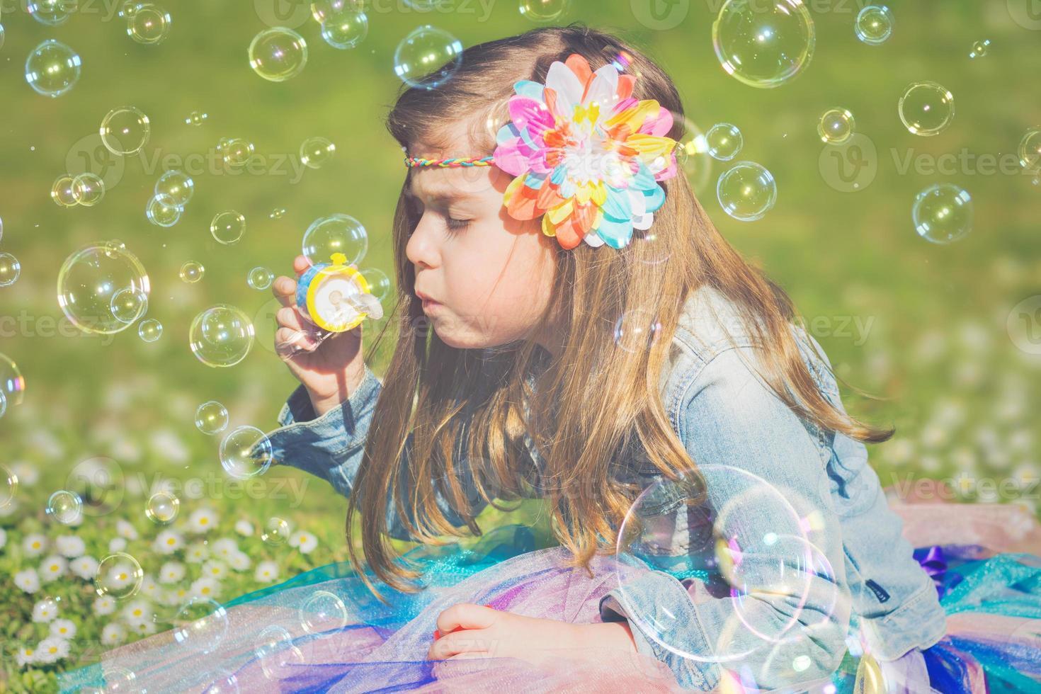 liten flicka som har kul, blåser såpbubblor foto