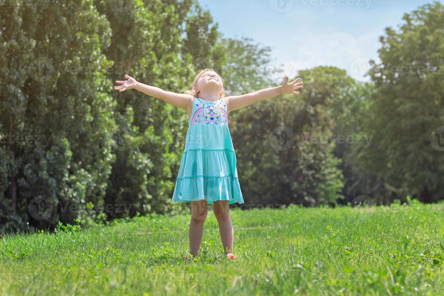 liten flicka med vidöppna armar, i parkens liv och natur foto