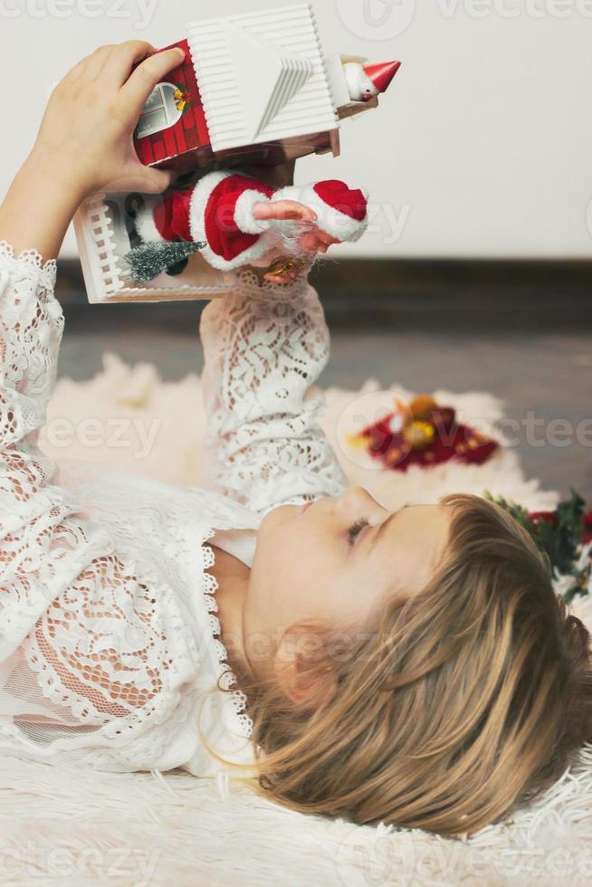 söt liten flicka som lägger på golvet, leker med juldekoration, lilla jultomten kommer ur lådan foto