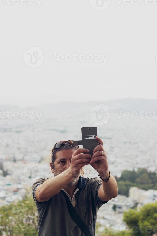 man tar en selfie på kullen, stadsbilden är i bakgrunden foto