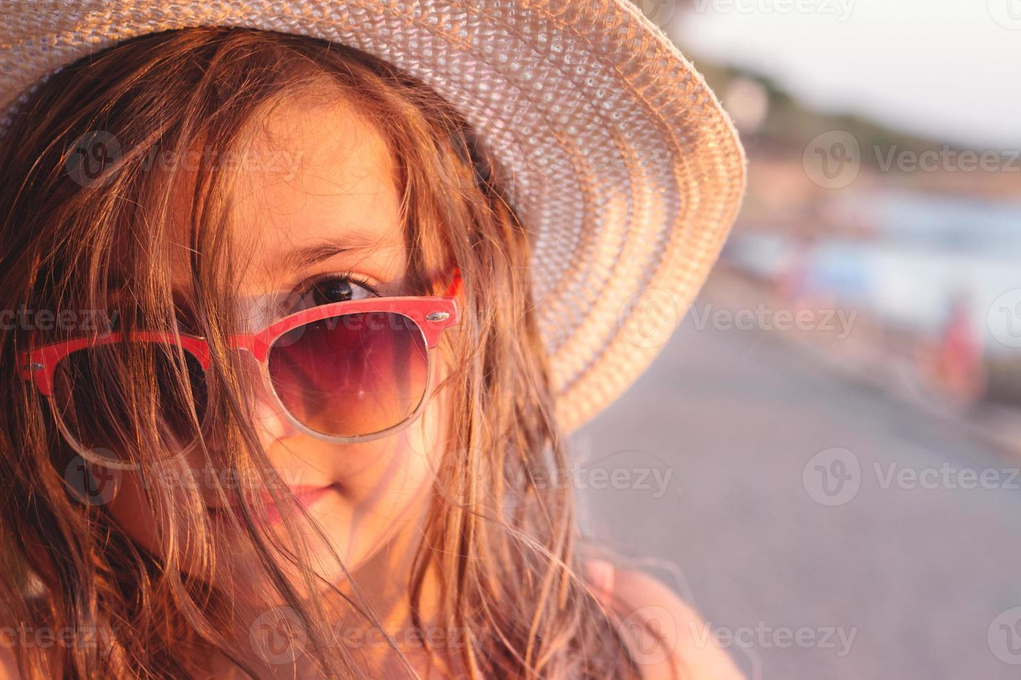 porträtt av en vacker liten flicka med solglasögon och stråhatt på stranden, med kopia utrymme foto