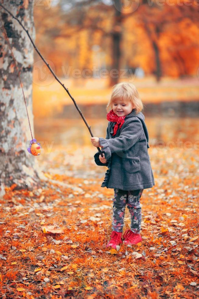 vacker liten flicka som leker med en gren och en fiskleksak, i parken en kall höstdag foto