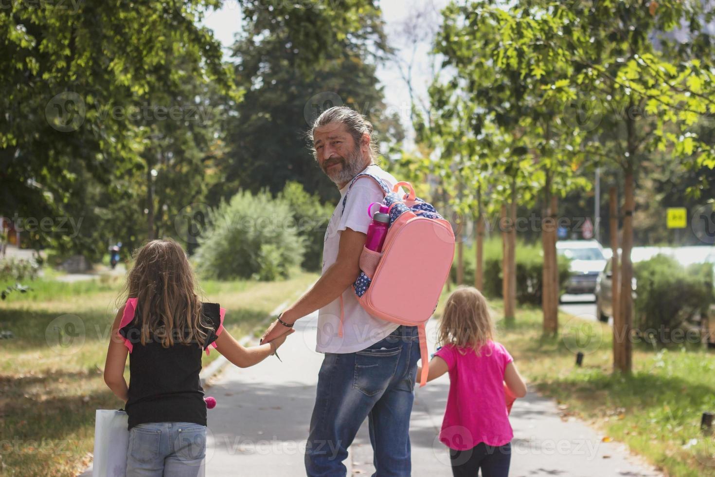 far tar med sina döttrar till skolan och bär barnväskan på ryggen foto
