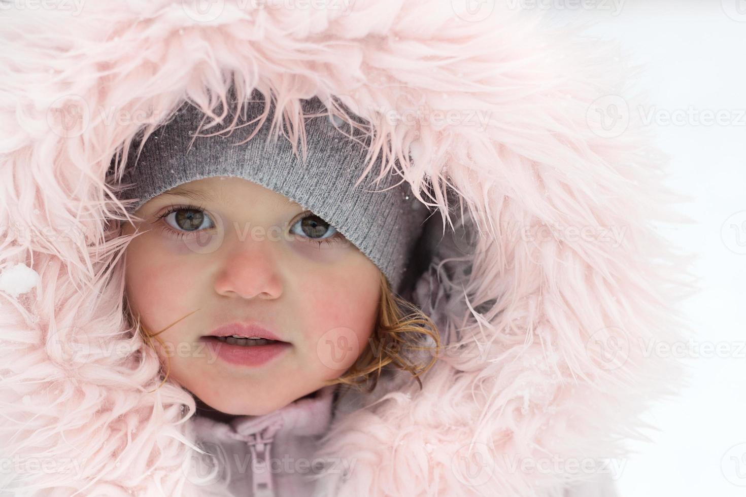 vinterporträtt av en vacker liten flicka på en snöig dag foto