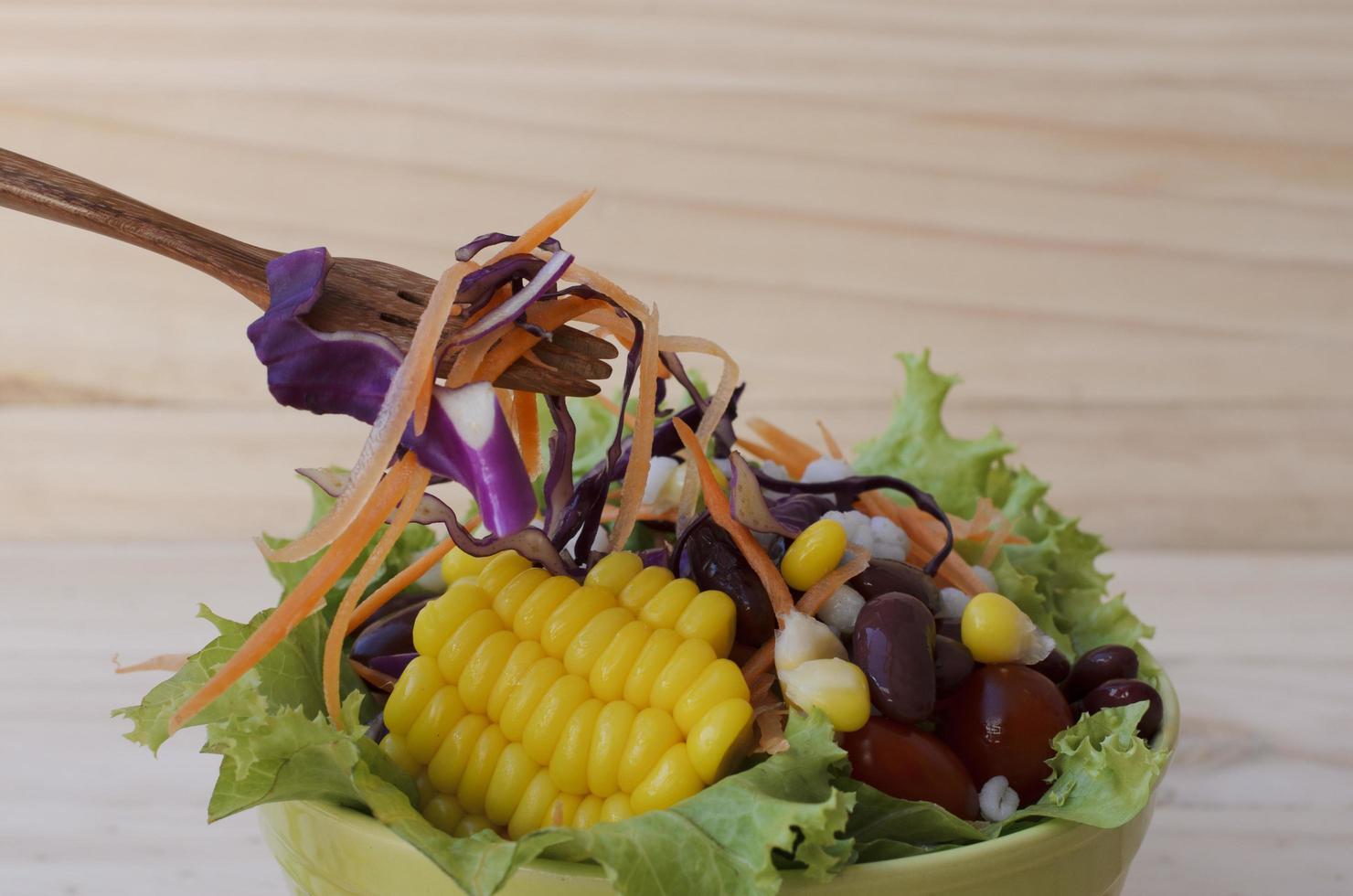 läcker färsk grönsaksallad med en trägaffel foto