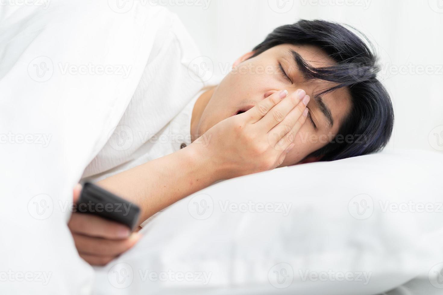 asiatisk man som ligger i sängen och använder telefonen. sömnig medan du använder telefonen foto