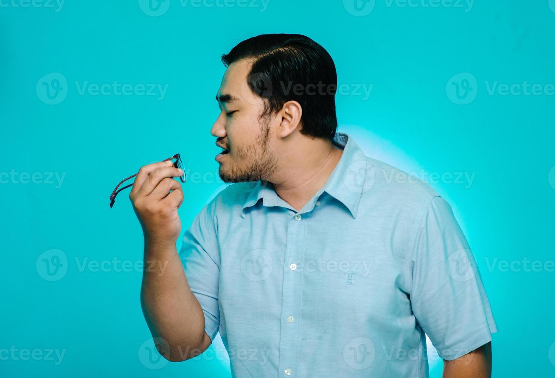 ung man som blåser glasögon i handen på blå bakgrund foto