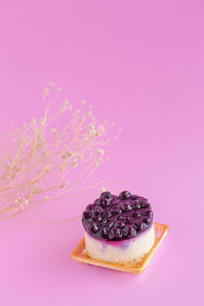 blåbärostkaka på en rosa bakgrund och kopieringsutrymme foto