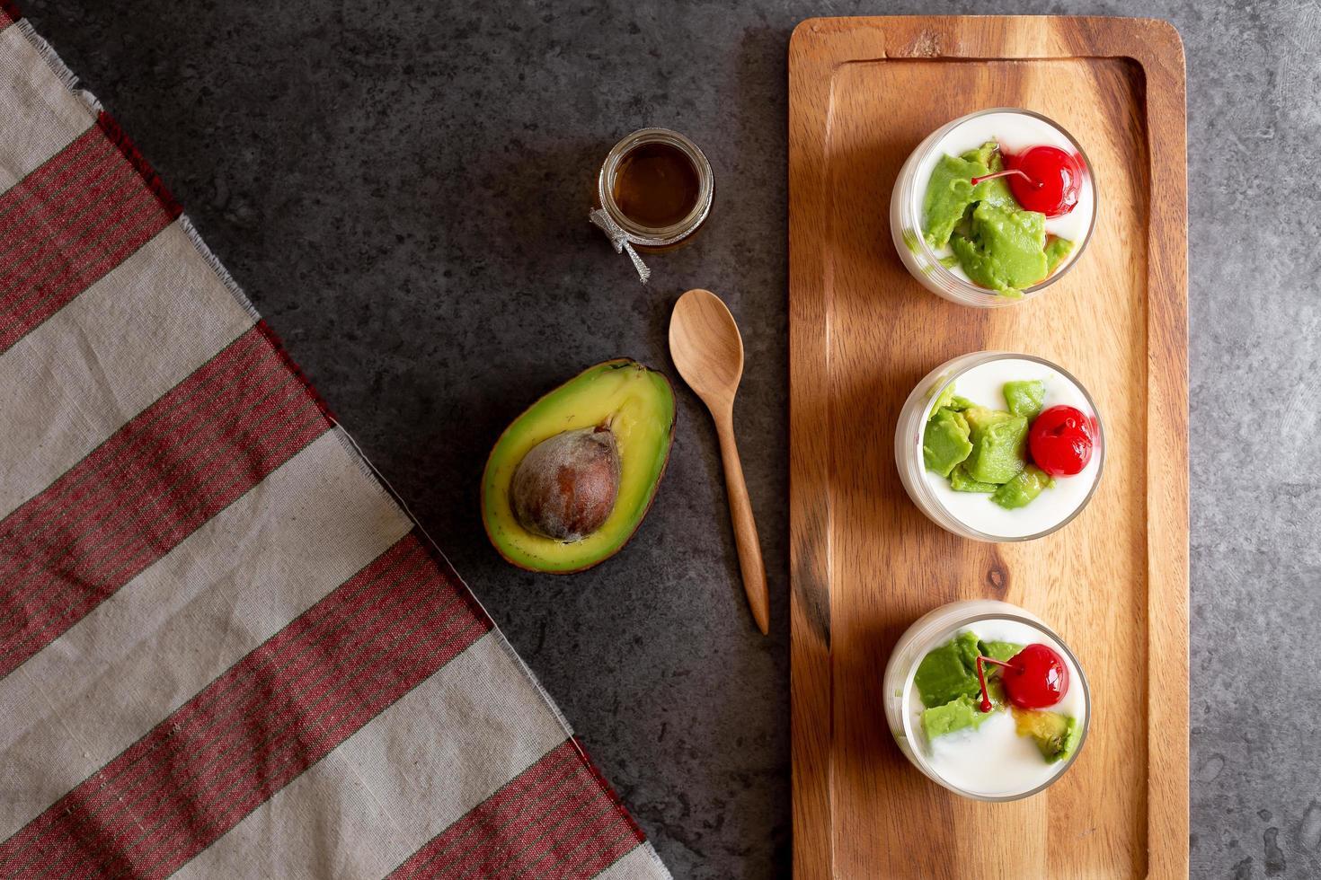 glas körsbär och avokado skivad i yoghurt på träbakgrund foto