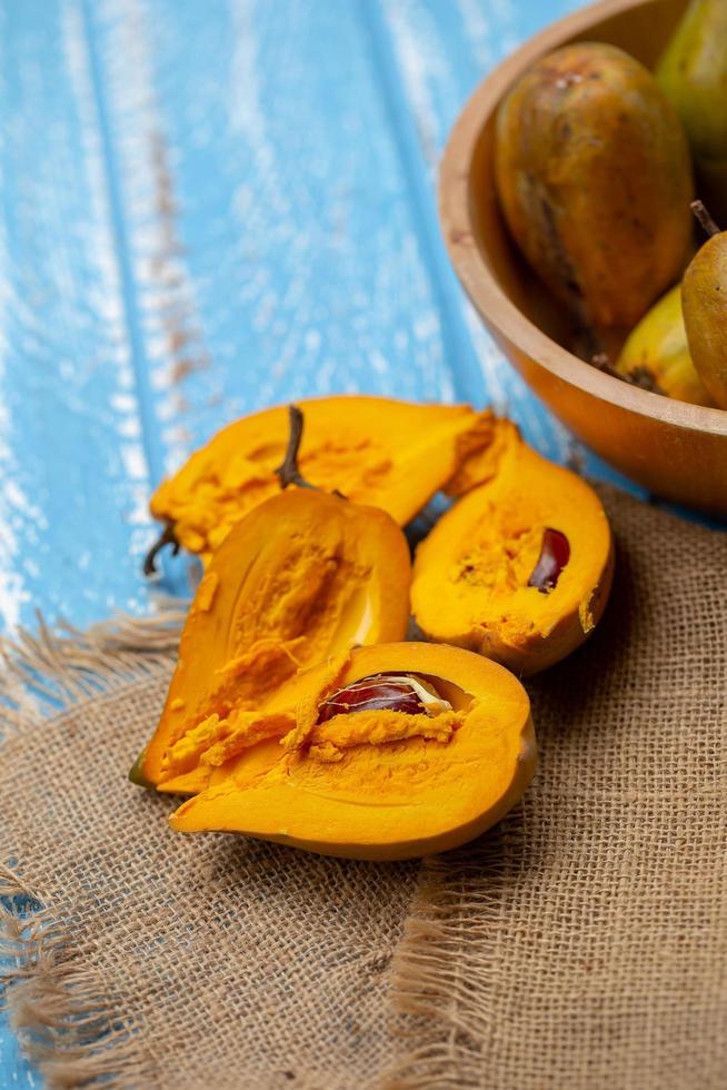 äggfrukt canistel gul sapote pouteria campechiana kunth baehni på blå träbord foto