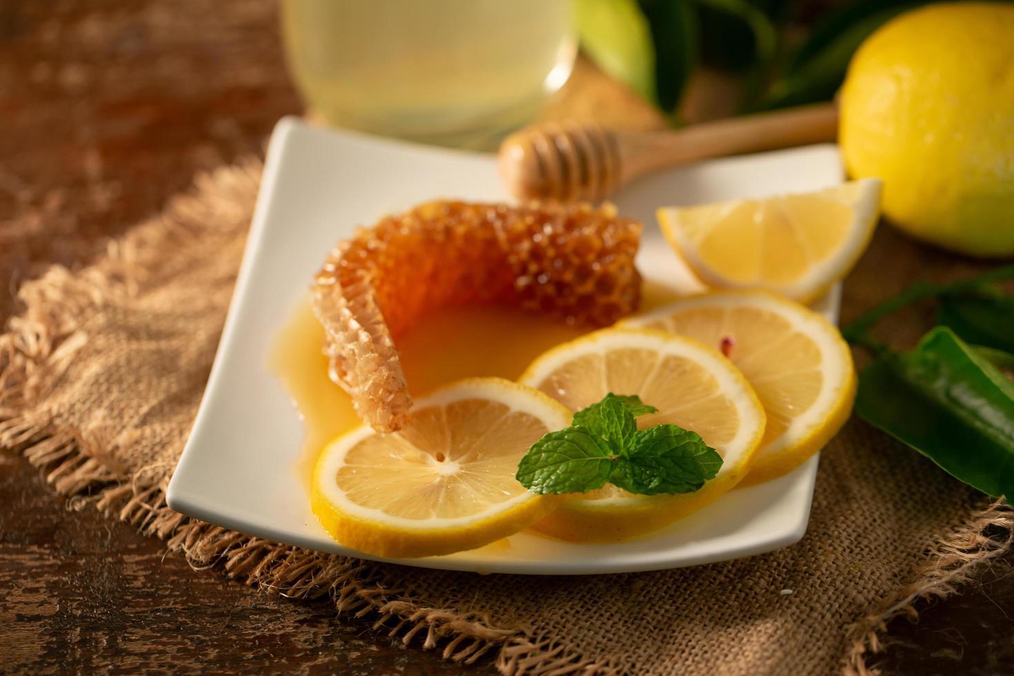 citronsaft med honung på träbord, citroner och salvia löv foto
