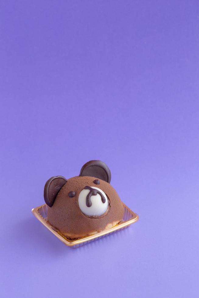 brun nallebjörns chokladchiffongkaka på en violett bakgrund och kopieringsutrymme foto