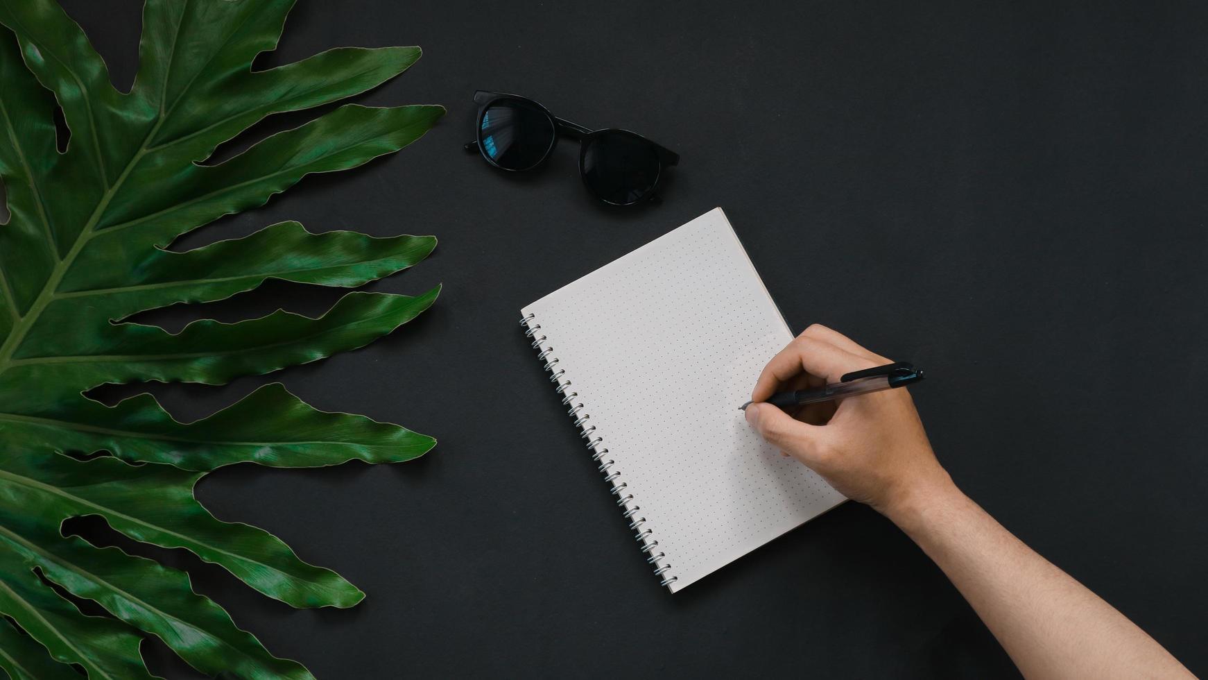 gröna blad hand med anteckningsboken på svart bakgrund foto