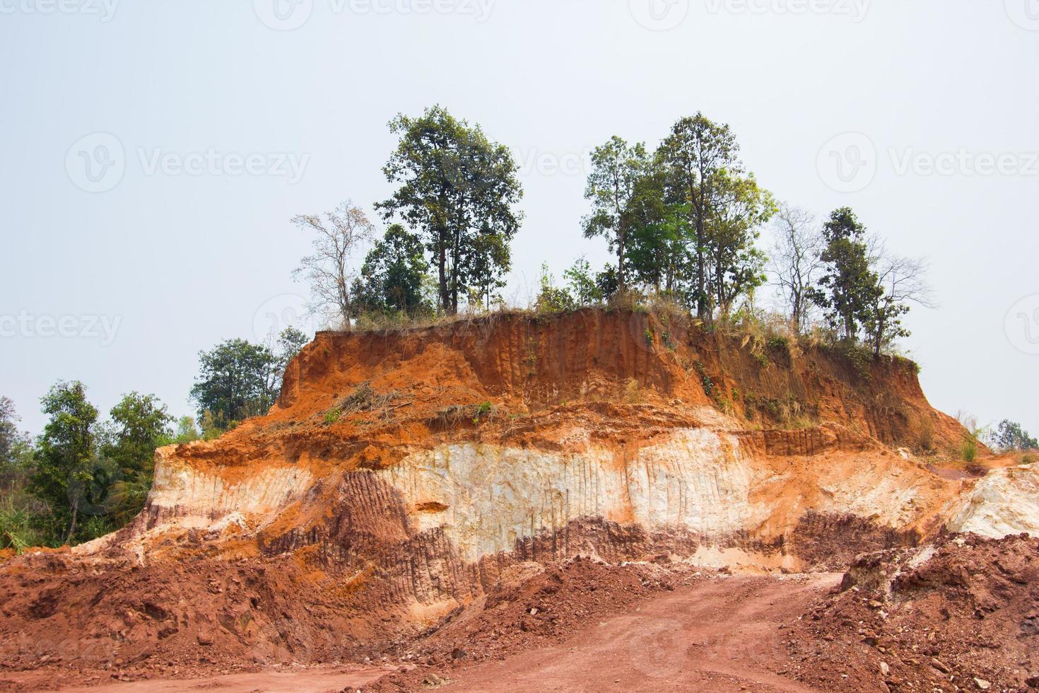 lager av jord frontlastare remsor hela sidan av en kulle foto