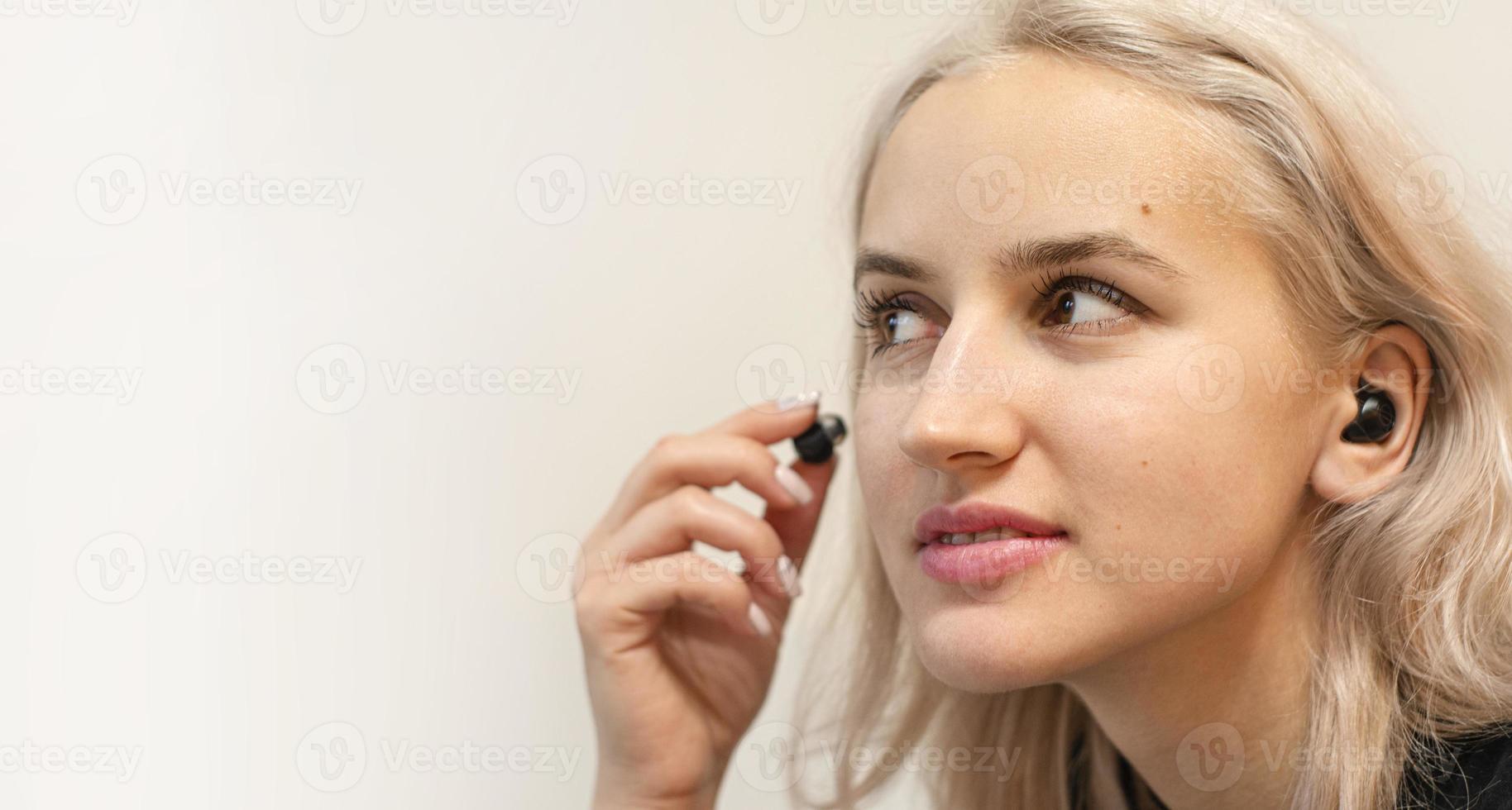 flickan sätter på trådlösa hörlurar. modern teknik. foto