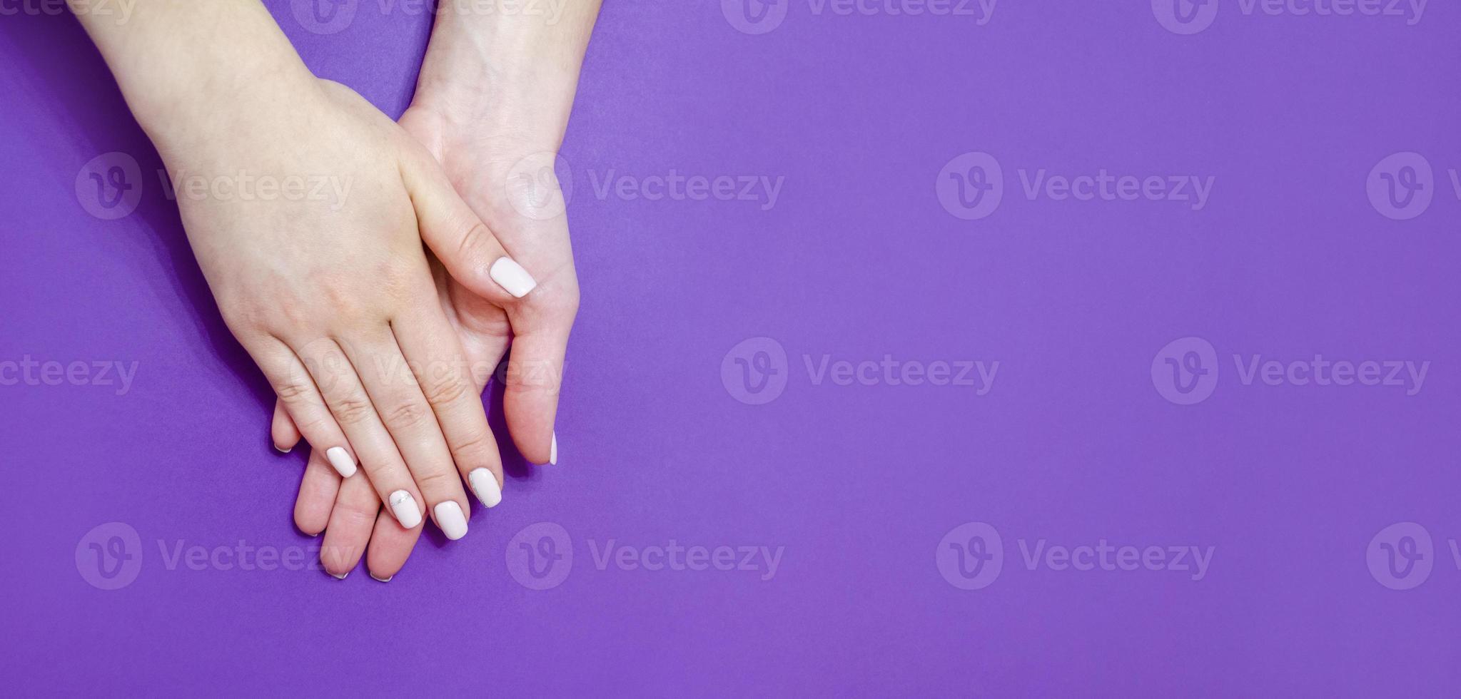kvinnlig manikyr på en ljus bakgrund. lila foto