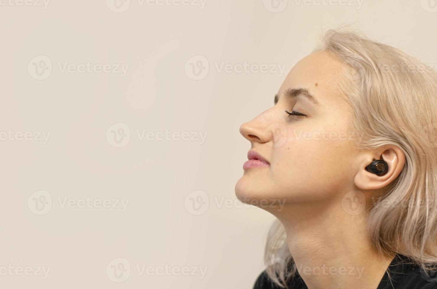 flicka tycker om musik i trådlösa hörlurar. modern teknik. foto