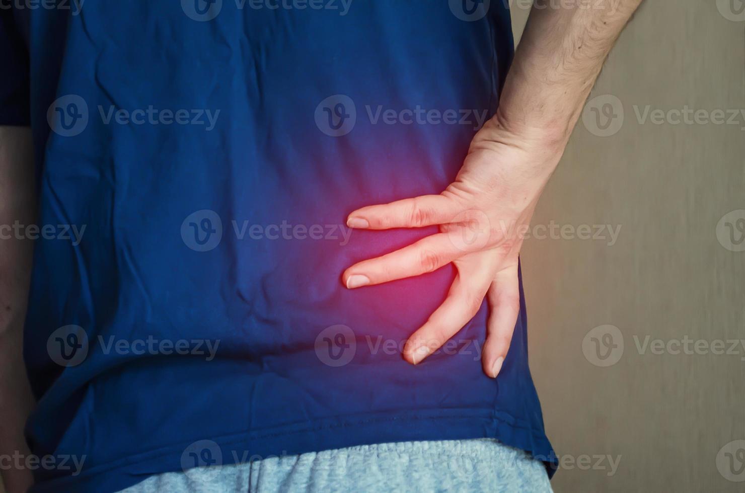 en man som håller ryggen. ryggont. foto