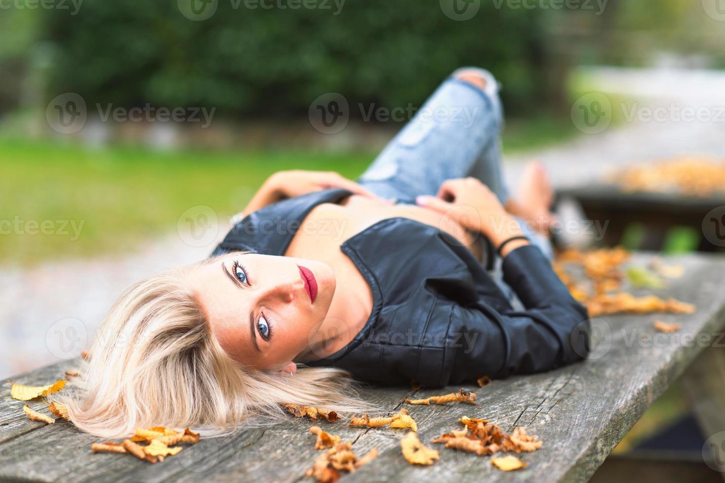 sexig blond naken flicka som ligger på en träbänk i höst foto