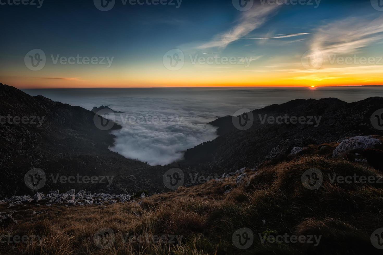 solnedgång i bergen med havet av låga moln foto