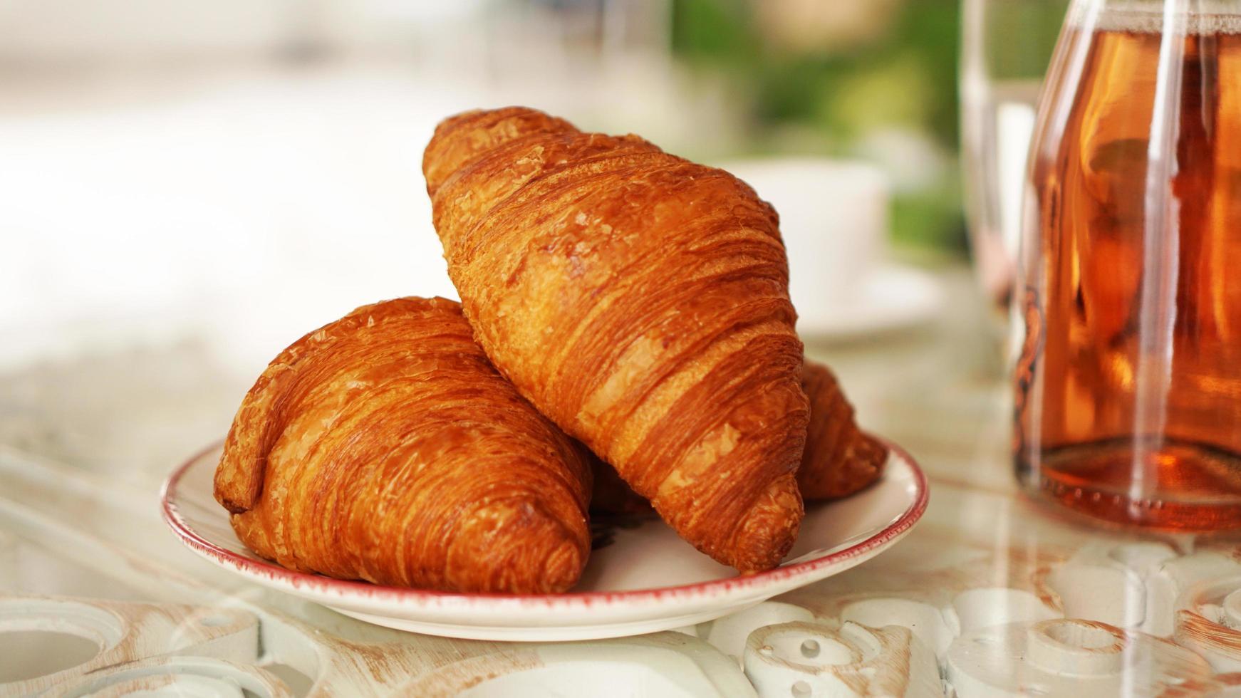 två färska croissanter på en tallrik på ett glasbord. frukost koncept foto