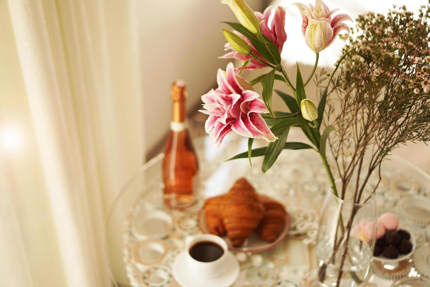 bukett liljor. kopp kaffe, croissanter och vin foto