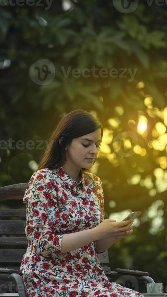 skönhet latin ung kvinna i vit blommig klänning läser på smartphone foto