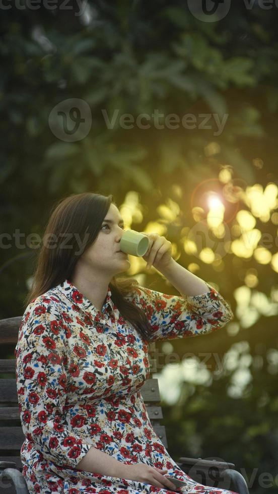 ung kvinna i en blommig klänning som dricker en kopp kaffe foto