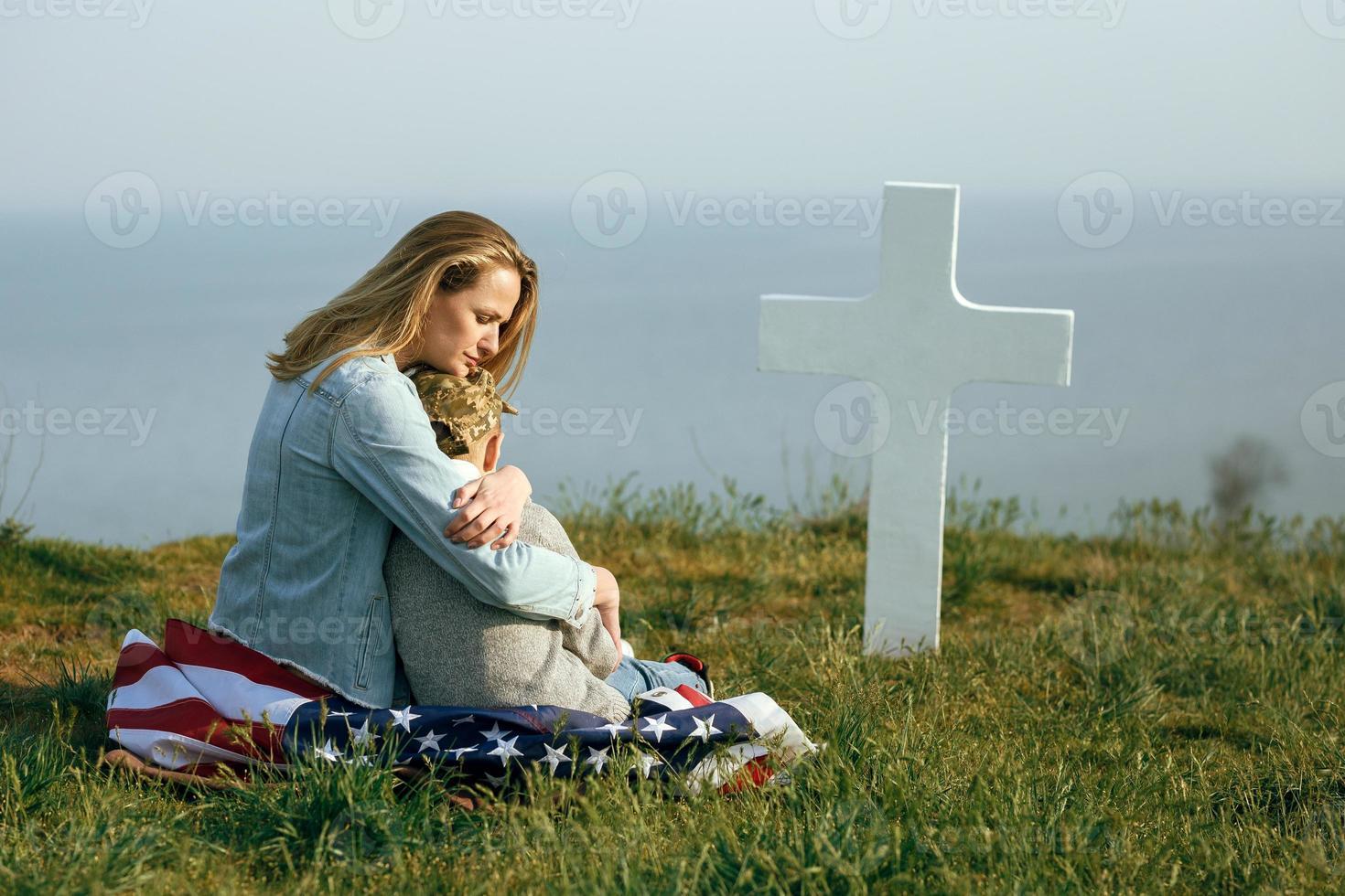 mamma och son sitter på en soldats grav foto