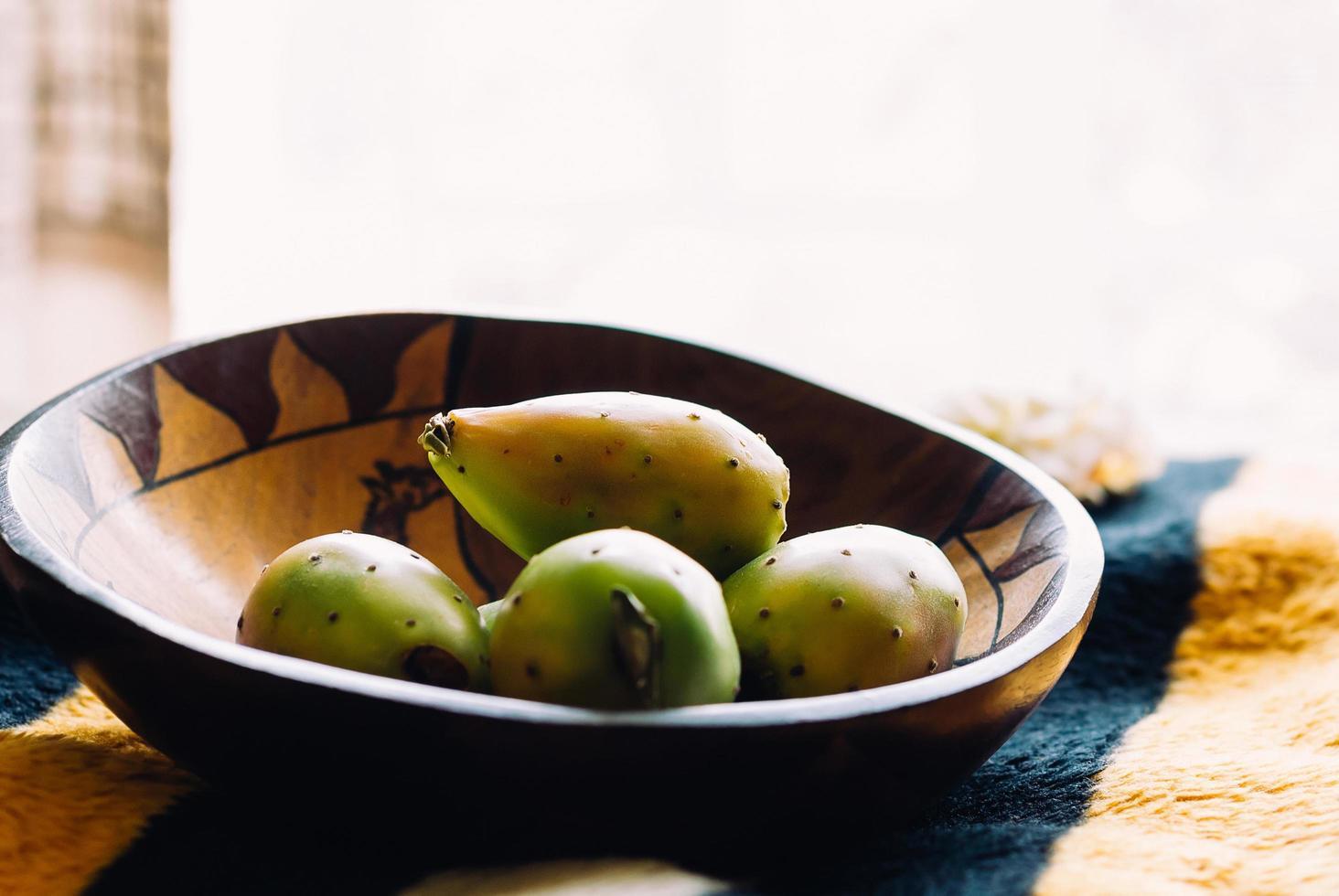 färska kaktuspäron i en träskål, selektivt fokus, dagsljus från fönstret. exotisk frukt för din hälsosamma kost foto