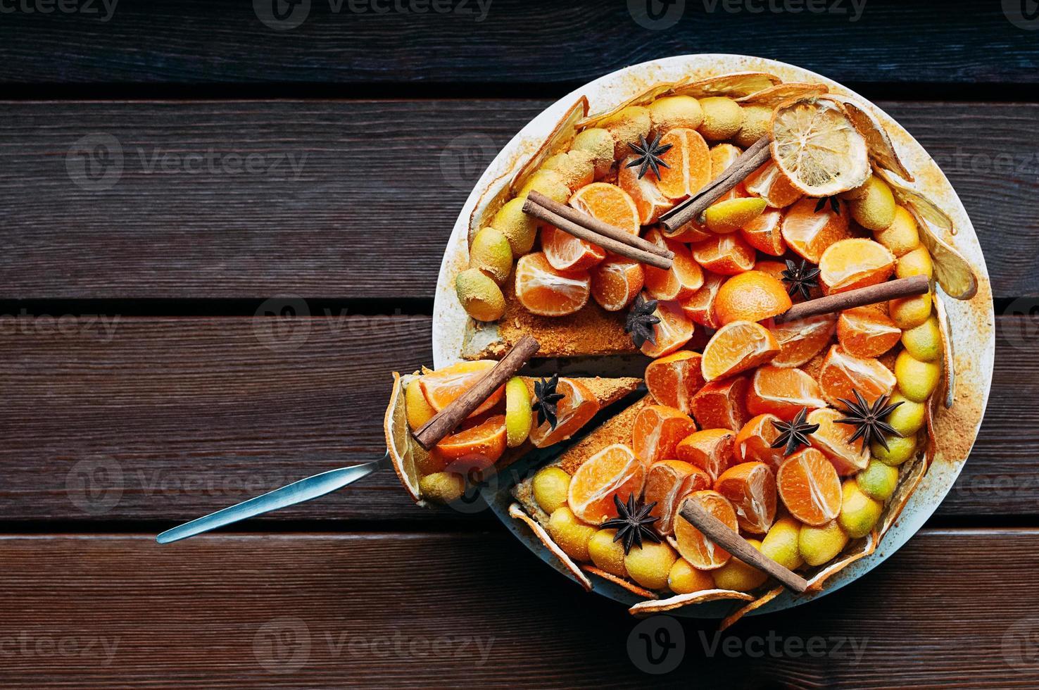 utsökt vegan citruskaka dekorerad med färska apelsiner och torra kryddor på brunt träbord. hel, en skiva skuren. färgglada, friska och saftiga. ovanifrån, utrymme för text eller design, för cafémeny eller konfektyrkatalog foto