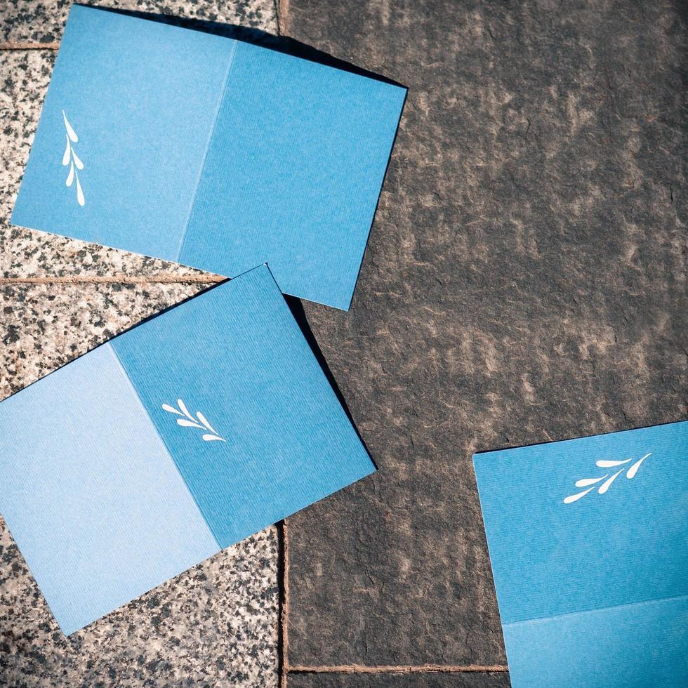 tomma blå inbjudningskort på grå textur för att ersätta din design, fyrkantiga format foto