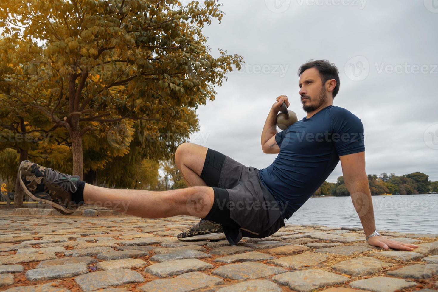 manlig fitnessinstruktör som bygger muskler med vattenkokare i parken foto