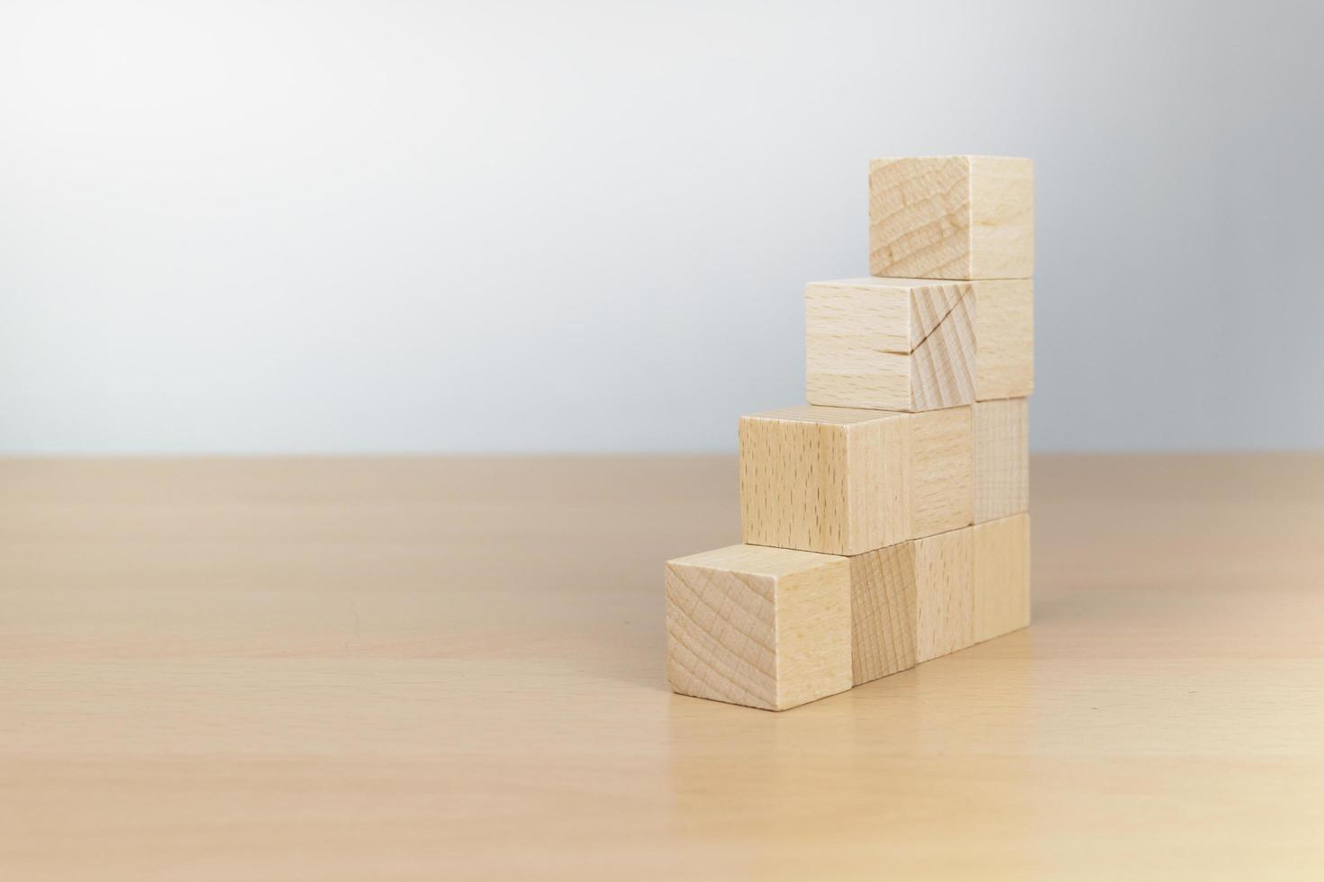 hand ordna träblockstapling som trappsteg på träbord foto