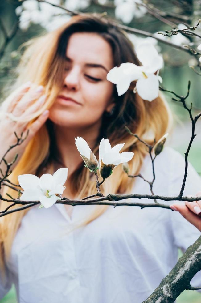 suddig bild av vacker flicka som njuter av magnolia blommor, stängda ögon foto