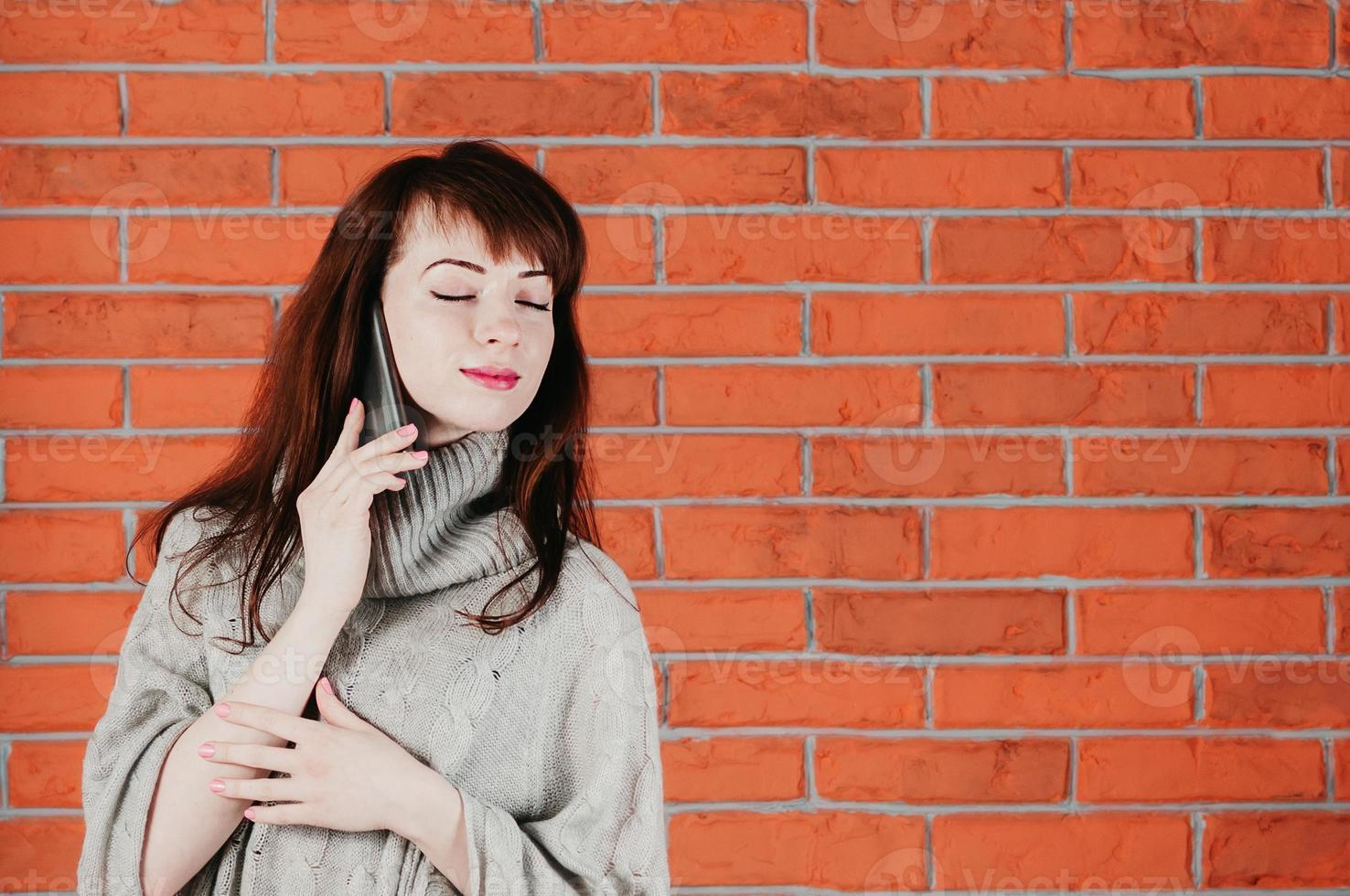 vacker tjej pratar med mobiltelefon, ögonen stängda, drömmande leende foto