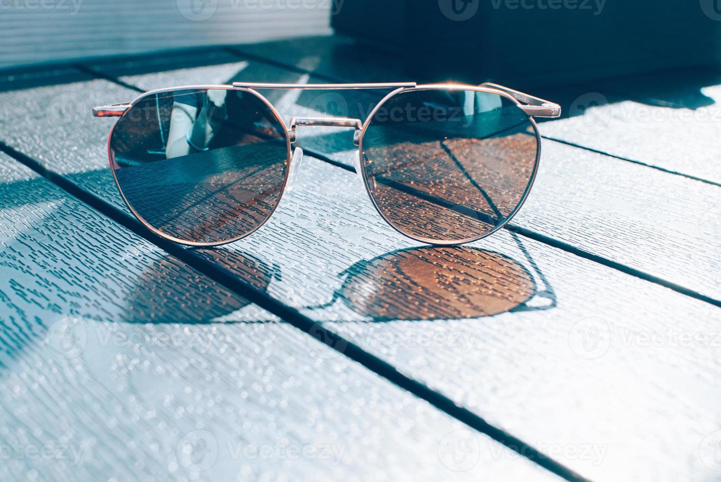 trendiga bruna solglasögon, blå nyanser på bordet foto
