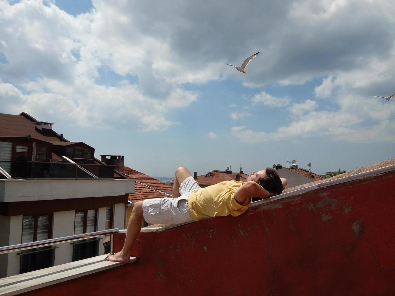 person som kopplar av på taket på sommardag foto