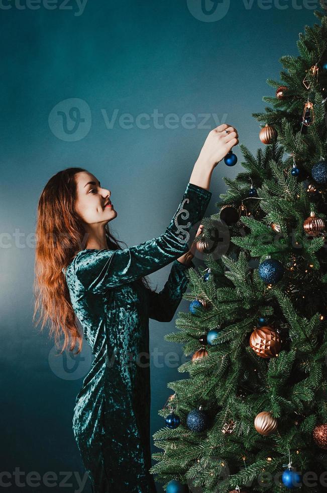attraktiv leende kvinna som dekorerar julgran foto