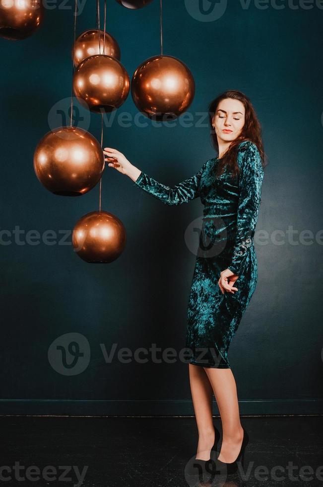 vacker ung kvinna i grönblå sammetsklänning, poserar foto