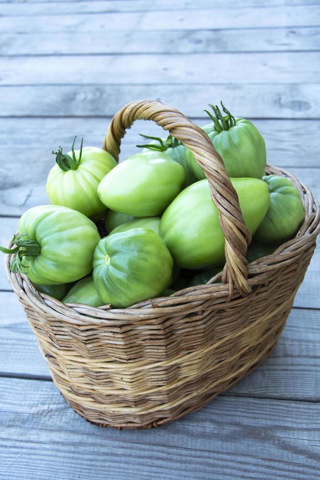 en korg med gröna tomater foto