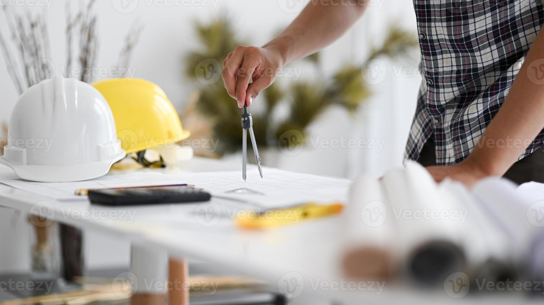 man hand använder en rondell för att skriva på en husplan. foto