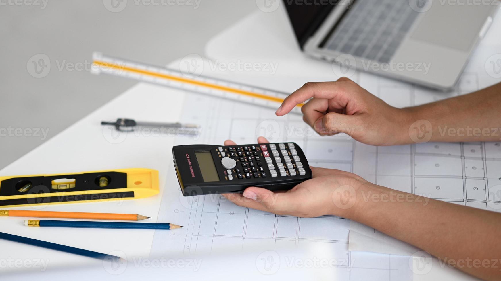 ingenjörer använder en miniräknare för att beräkna husplaner. foto