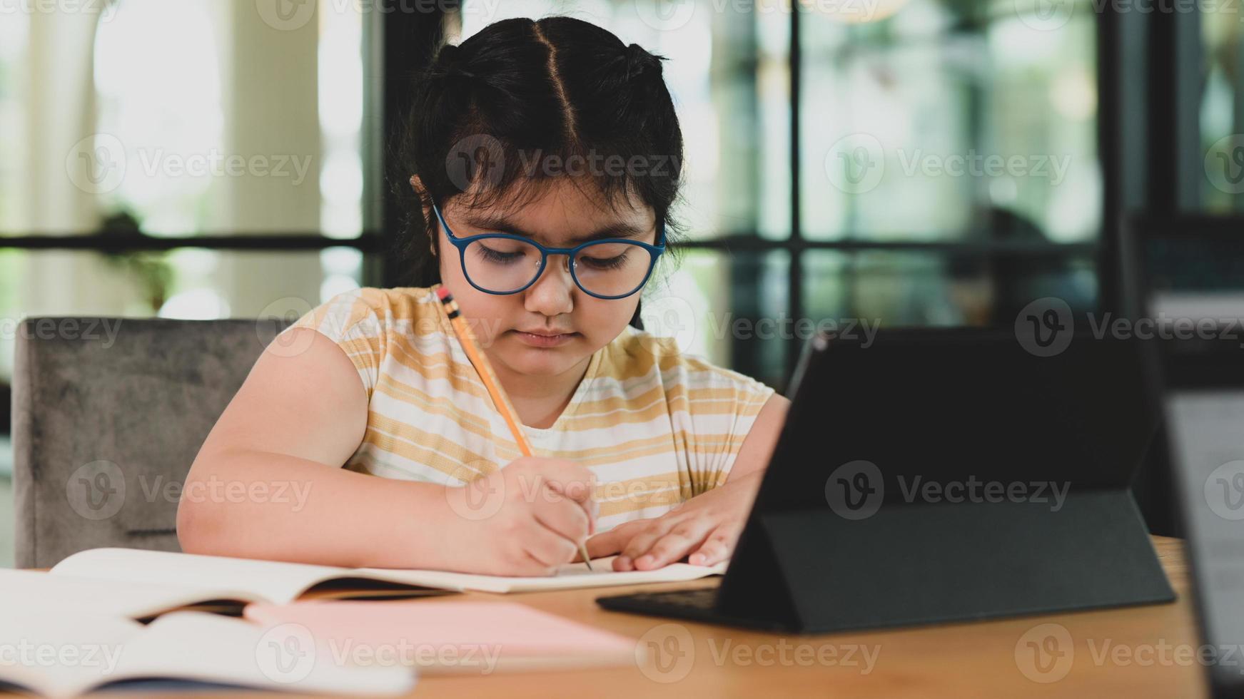 asiatisk flicka med glasögon gör sina läxor i en anteckningsbok. foto