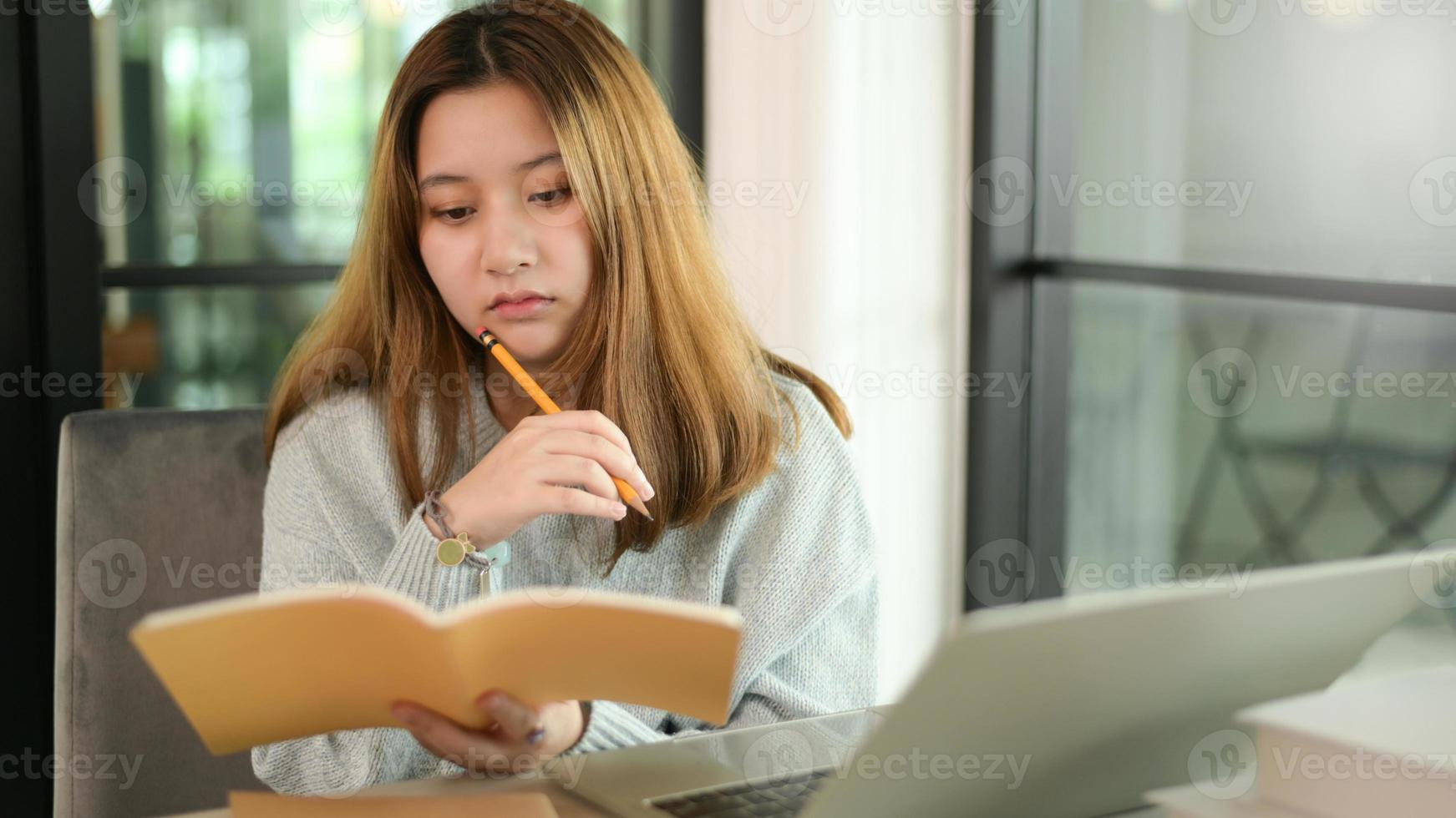 tonårskvinna som håller penna och anteckningsbok allvarlig gest med bärbar dator. foto