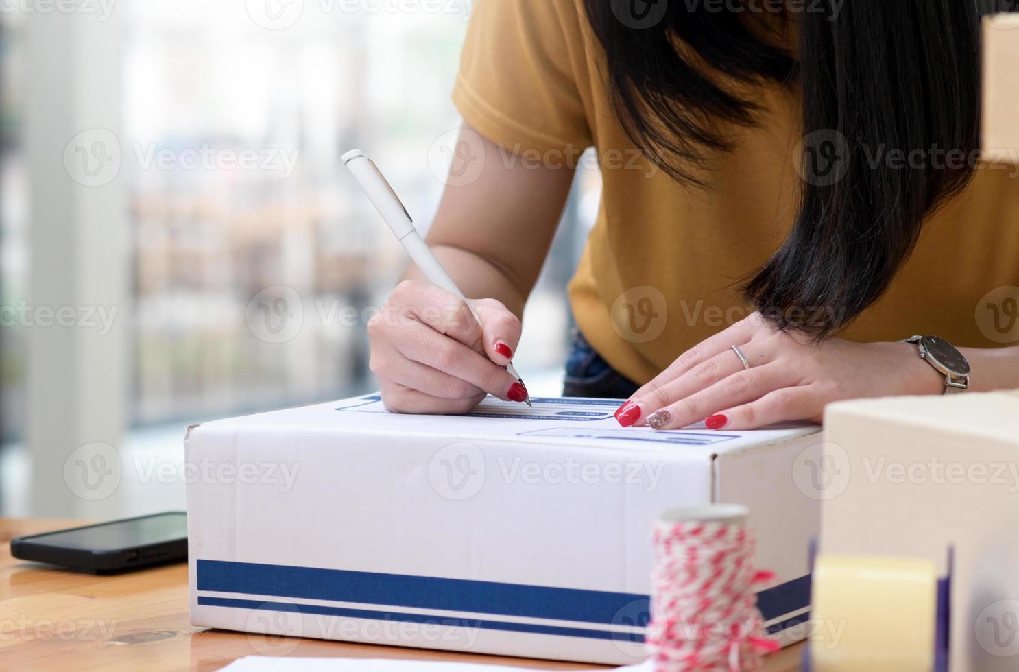 flickan skrev adressen på kartongen för att leverera paketet. foto