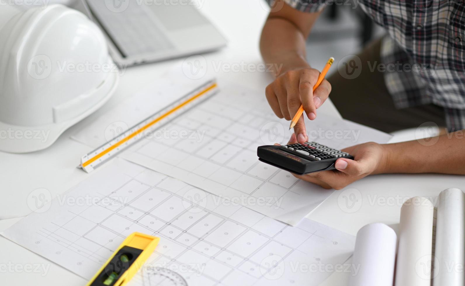 arkitekter använder en kalkylator för att uppskatta kostnaden för husplaner. foto
