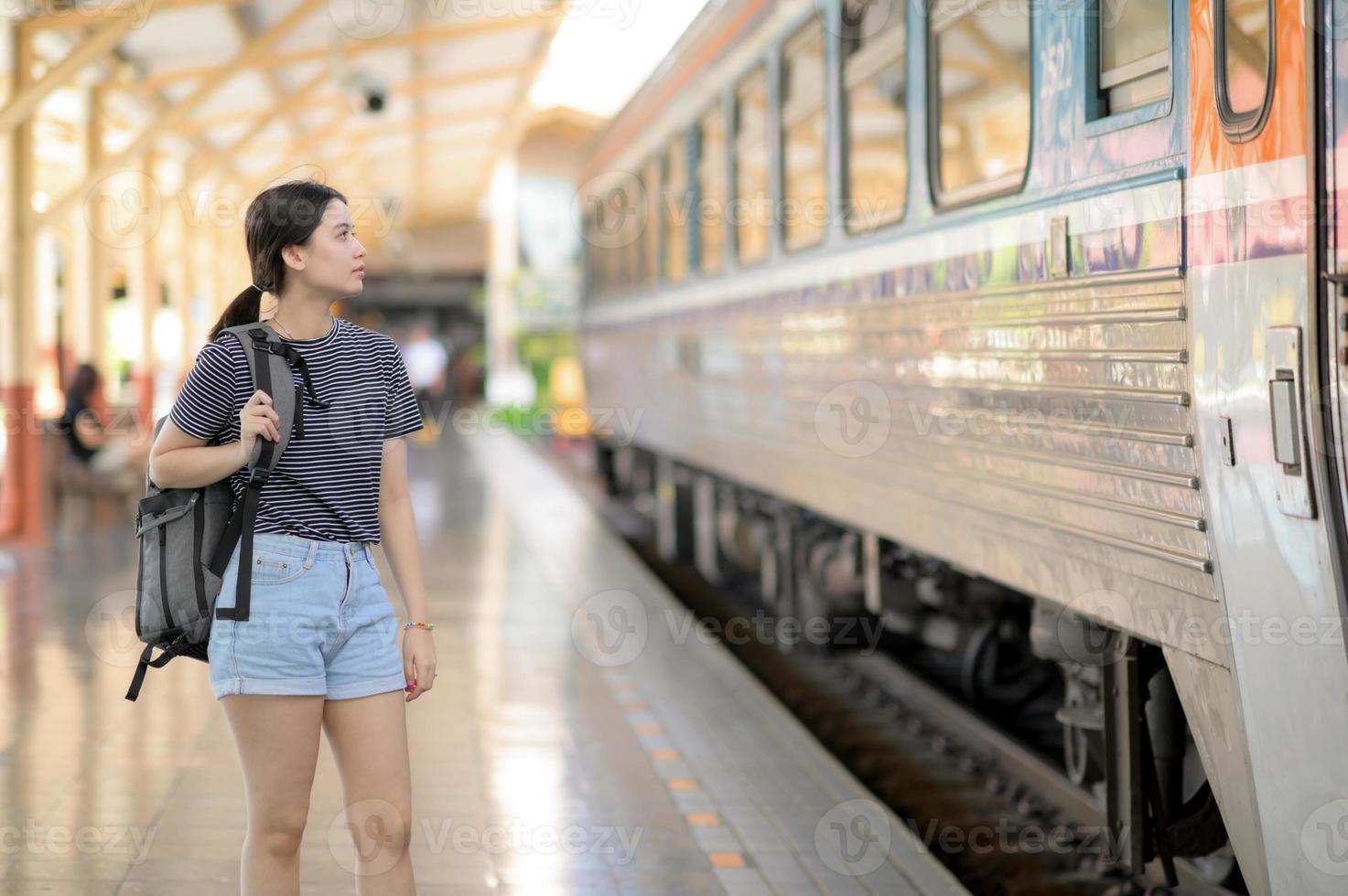 en kvinnlig internationell resenär med ryggsäck väntar på tåget. foto